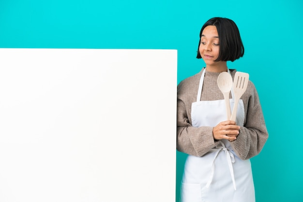 Young mixed race cook woman with a big placard isolated on blue background having doubts while looking side