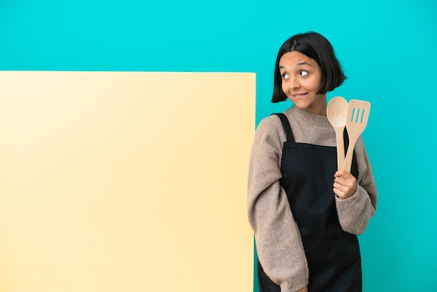 Young mixed race cook woman with a big placard isolated on blue background having doubts while looking up