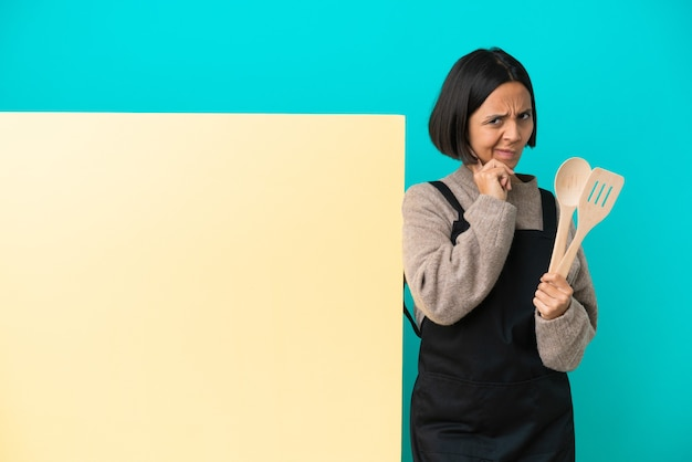 Young mixed race cook woman with a big placard isolated on blue background having doubts
