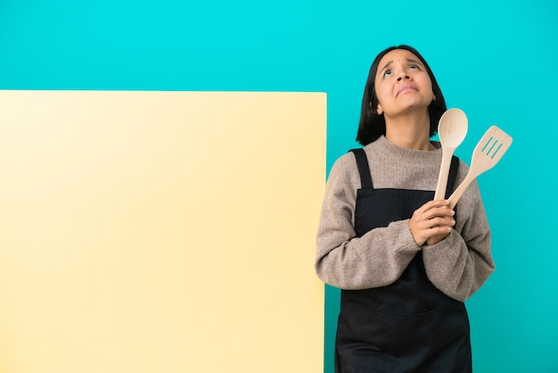 Young mixed race cook woman with a big placard isolated on blue background keeps palm together. person asks for something