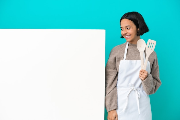 Young mixed race cook woman with a big placard isolated on blue background looking up while smiling