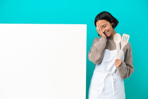 Young mixed race cook woman with a big placard isolated on blue background smiling a lot