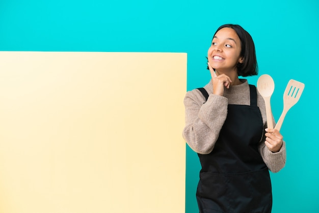 Young mixed race cook woman with a big placard isolated on blue background thinking an idea while looking up