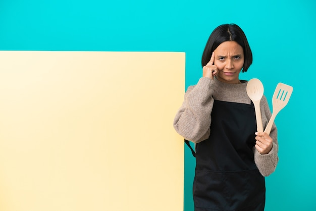 Young mixed race cook woman with a big placard isolated on blue background thinking an idea