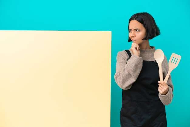 Young mixed race cook woman with a big placard isolated on blue wall thinking an idea while looking up