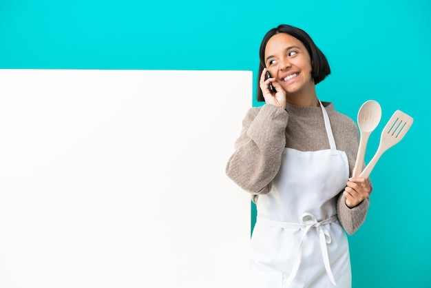 Young mixed race cook woman with a big placard isolated keeping a conversation with the mobile phone