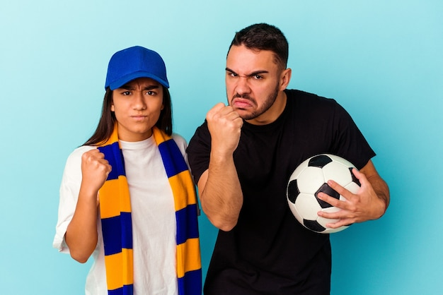 Young mixed race couple cleaning home isolated on blue background showing fist to camera, aggressive facial expression.