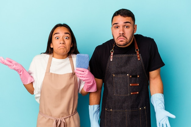 Young mixed race couple cleaning home isolated on blue background shrugs shoulders and open eyes confused.