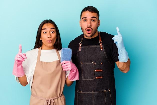 Молодая пара смешанной расы, уборка дома, изолированные на синем фоне, имея отличную идею, концепцию творчества.