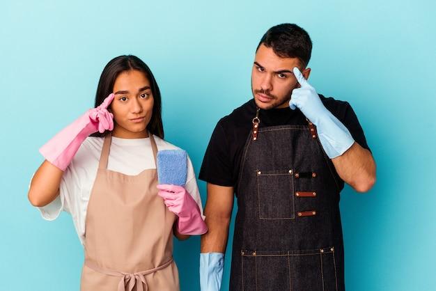 Молодая пара смешанной расы, уборка дома, изолированные на синем фоне, указывая висок пальцем, думая, сосредоточилась на задаче.