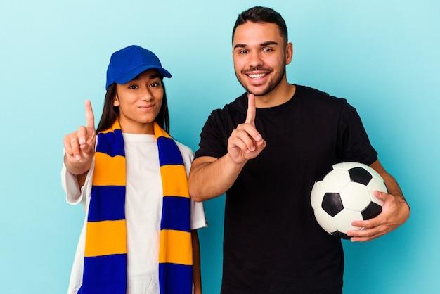 Молодая пара смешанной расы уборка дома изолирована на синем фоне, показывая номер один пальцем.