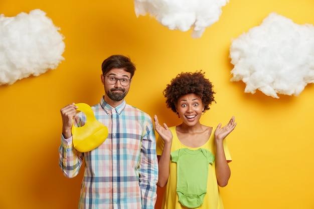 젊은 혼혈 부부는 아기를 기대하고, 미래의 아이를 위해 옷을 사고, 일 중항과 고무 턱받이로 포즈를 취하고, 출산 준비를하고, 노란색 위에 고립되어 있습니다. 행복한 미래의 부모는 집에서 포즈.