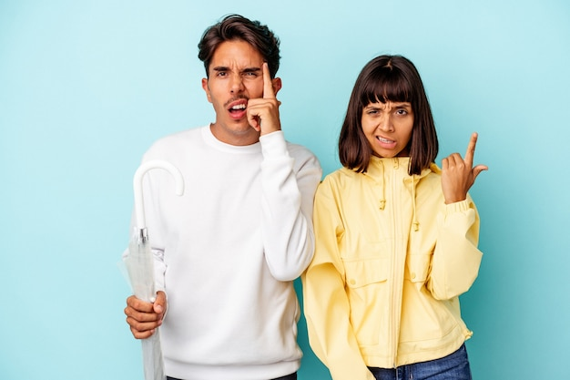 Young mixed race couple holding umbrella isolated on blue background showing a disappointment gesture with forefinger.