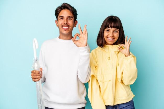 Молодая пара смешанной расы, держащая зонтик на синем фоне, веселая и уверенная, показывая хорошо жест.