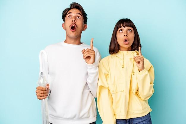 Молодая пара смешанной расы, держащая зонтик, изолированные на синем фоне, указывая вверх с открытым ртом.