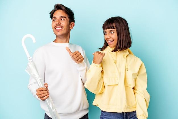 Молодая пара смешанной расы, держащая зонтик, изолированный на синем фоне, указывает пальцем далеко, смеясь и беззаботно.