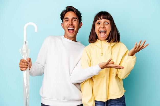 Молодая пара смешанной расы держит зонтик на синем фоне, получая приятный сюрприз, взволнованный и поднимающий руки.