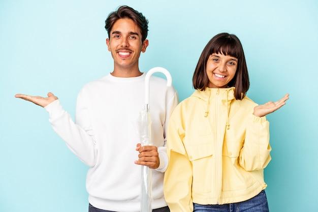 Молодая пара смешанной расы держит зонтик, изолированный на синем фоне, показывая копию пространства на ладони и держа другую руку на талии.