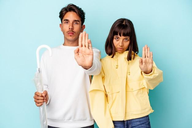 青の背景に孤立した傘を持っている若い混血カップルは、一時停止の標識を示す伸ばした手で立って、あなたを防ぎます。