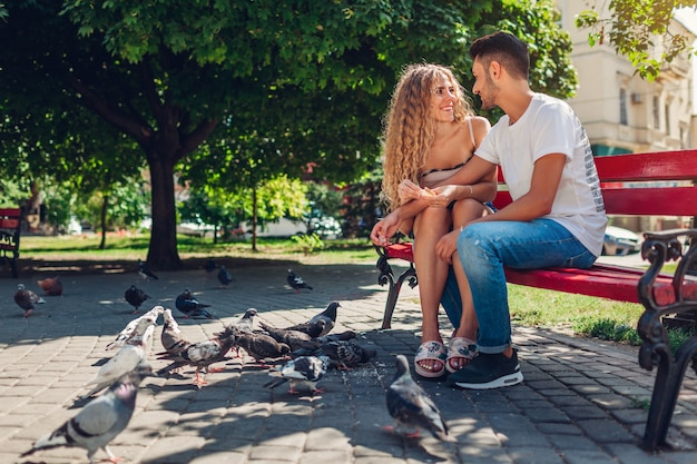 夏の公園で入札者を養う愛の若い混血カップル。アラブ人と白人女性が鳩にパンを投げて話している