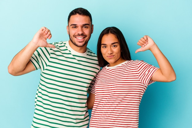 Young mixed race couple isolated on blue background feels proud and self confident, example to follow.