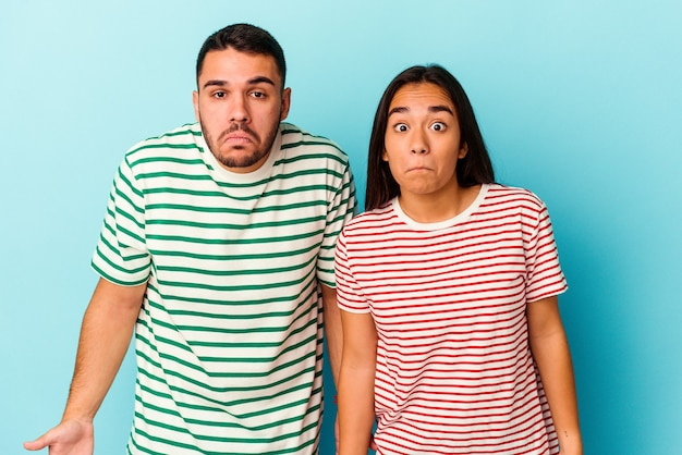 Young mixed race couple isolated on blue background shrugs shoulders and open eyes confused.