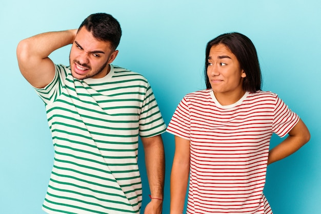 Young mixed race couple isolated on blue background touching back of head, thinking and making a choice.