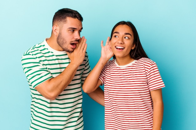 Young mixed race couple isolated on blue background trying to listening a gossip.