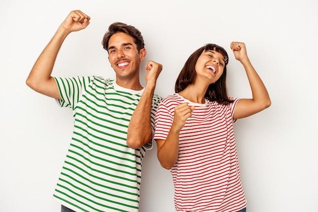 特別な日を祝う白い背景で隔離の若い混血カップルは、エネルギーでジャンプして腕を上げます。