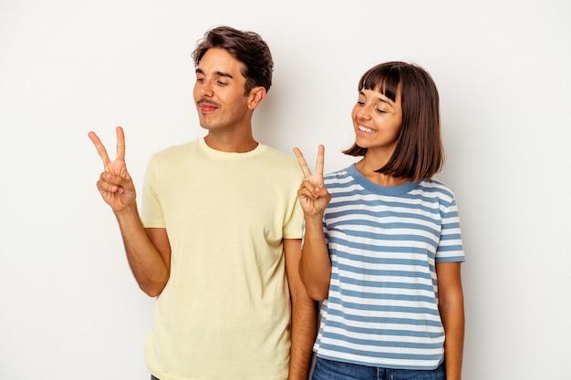 指で平和のシンボルを示す、楽しくてのんきな白い背景で隔離の若い混血カップル。