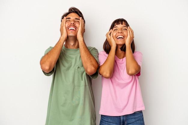 白い背景で隔離の若い混血カップルは、頭を抱えて喜んで笑います。幸福の概念。