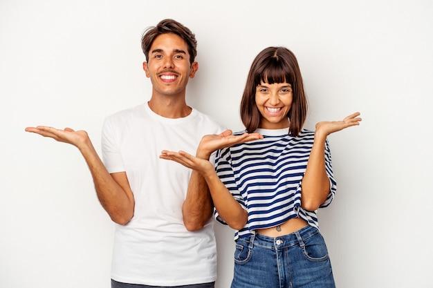白い背景で隔離の若い混血カップルは腕でスケールを作り、幸せで自信を持って感じます。