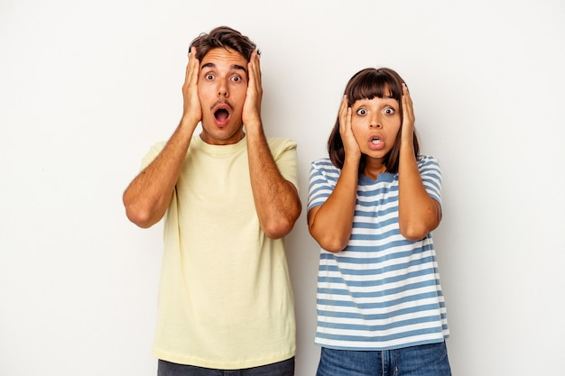 Young mixed race couple isolated on white background being shocked, she has remembered important meeting.