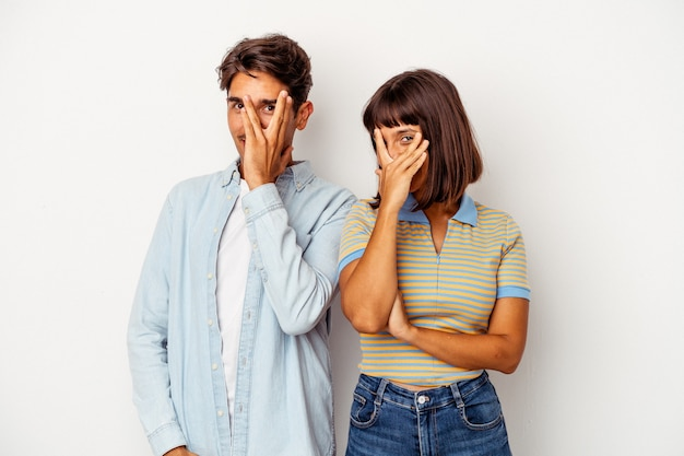 Young mixed race couple isolated on white background blink at the camera through fingers, embarrassed covering face.