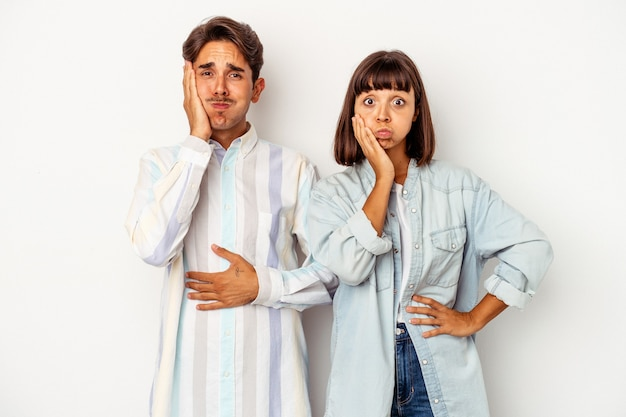Young mixed race couple isolated on white background blows cheeks, has tired expression. facial expression concept.