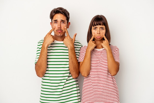 Young mixed race couple isolated on white background crying, unhappy with something, agony and confusion concept.
