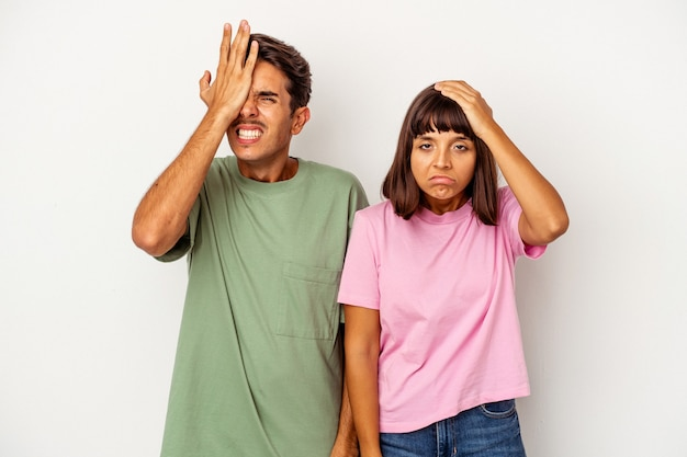 Young mixed race couple isolated on white background forgetting something, slapping forehead with palm and closing eyes.