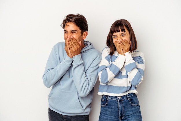 Young mixed race couple isolated on white background laughing about something, covering mouth with hands.