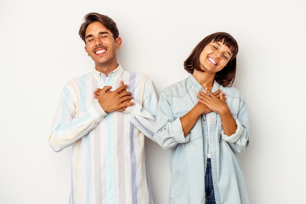 Young mixed race couple isolated on white background laughing keeping hands on heart, concept of happiness.