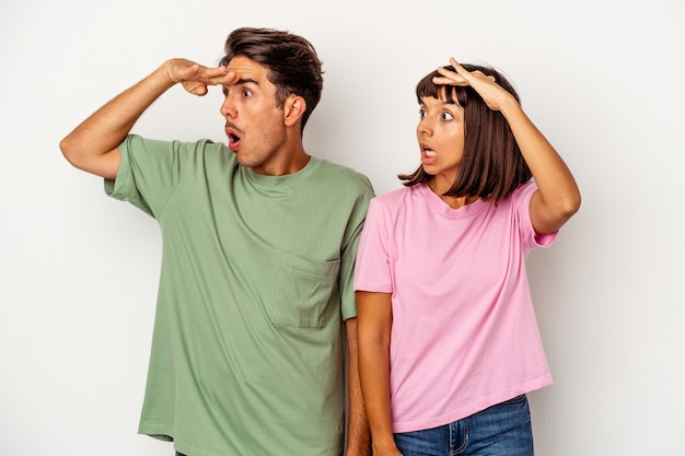 Young mixed race couple isolated on white background looking far away keeping hand on forehead.