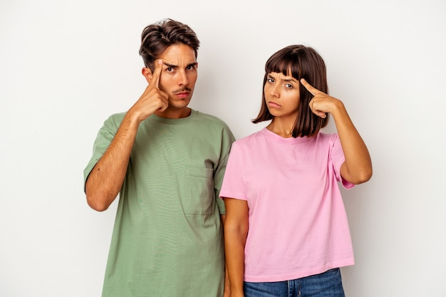 Young mixed race couple isolated on white background pointing temple with finger, thinking, focused on a task.