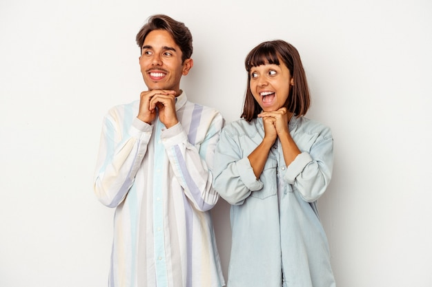 Young mixed race couple isolated on white background praying for luck, amazed and opening mouth looking to front.