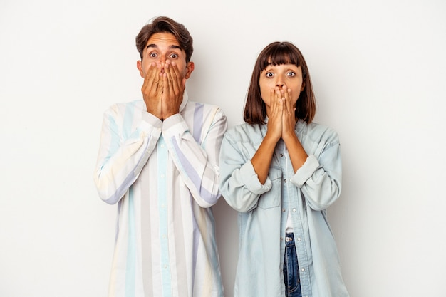 Young mixed race couple isolated on white background shocked, covering mouth with hands, anxious to discover something new.