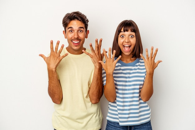 Young mixed race couple isolated on white background showing number ten with hands.
