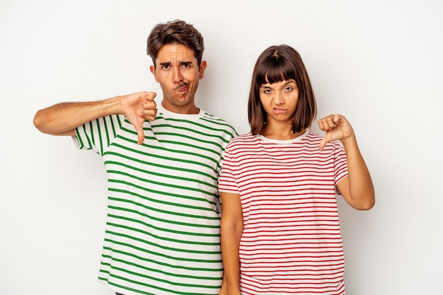 Young mixed race couple isolated on white background showing thumb down, disappointment concept.