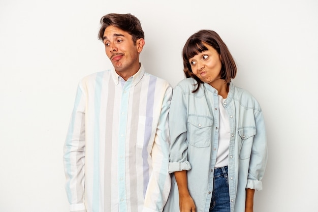 Young mixed race couple isolated on white background shrugs shoulders and open eyes confused.