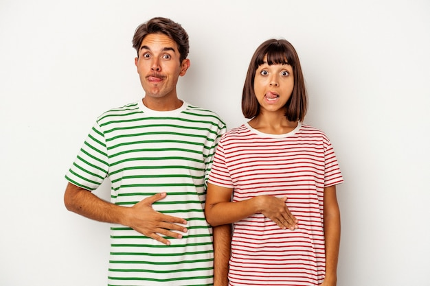 Young mixed race couple isolated on white background touches tummy, smiles gently, eating and satisfaction concept.