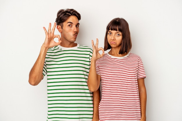 Young mixed race couple isolated on white background winks an eye and holds an okay gesture with hand.