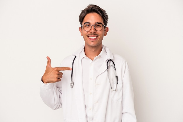 Young mixed race doctor man isolated on white background person pointing by hand to a shirt copy space, proud and confident