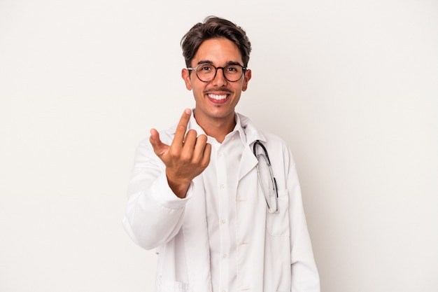 Young mixed race doctor man isolated on white background pointing with finger at you as if inviting come closer.